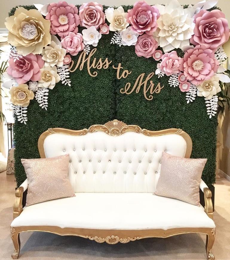 Dekorasi tunanga dengan latar belakang hijau penuh dengan bunga pink gold dan putih juga sofa besar sebagai inti point