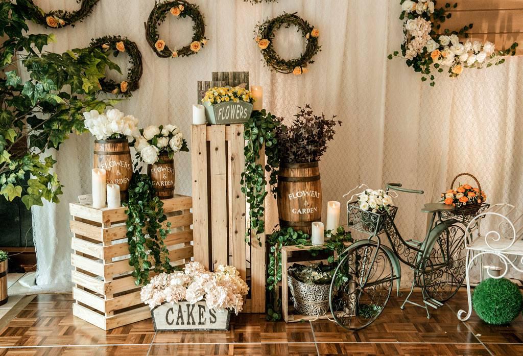 Tirai putih lembut dengan properti kembang hijau serta kayu palet dengan berbagai macam bentuk menjadi satu dekorasi tunangan yang cukup simpel
