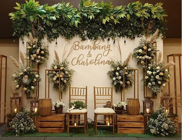 Dekorasi tunangan gold putih yang sangat epik ini menghadirkan nama kedua calon pasangan yang akan mengikat janji diacara keluarga