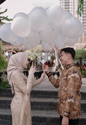 Foto wisuda couple dengan pasangan serta properti balon