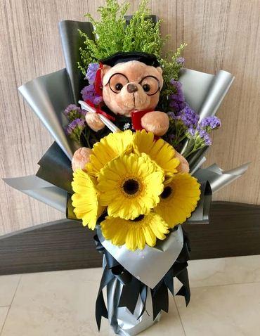 Buket bunga wisuda dengan karakter boneka lucu pakai kacamata.
